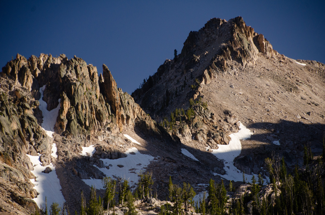 Best Baron Lakes Idaho Hikes - Grandjean Campground and Trailhead to Redfish Lake.  A section of the ridge surrounding the Baron Lakes can be seen at dusk, as shadows fall across snow patches and crumbling rock cliffs, Sawtooth Wilderness and National Recreation Area.