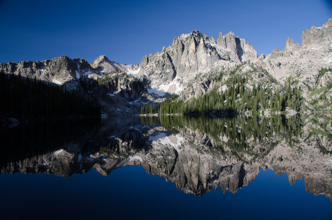 A view of middle Baron Lake at dawn.  The surrounding peaks reflect in the still morning water.