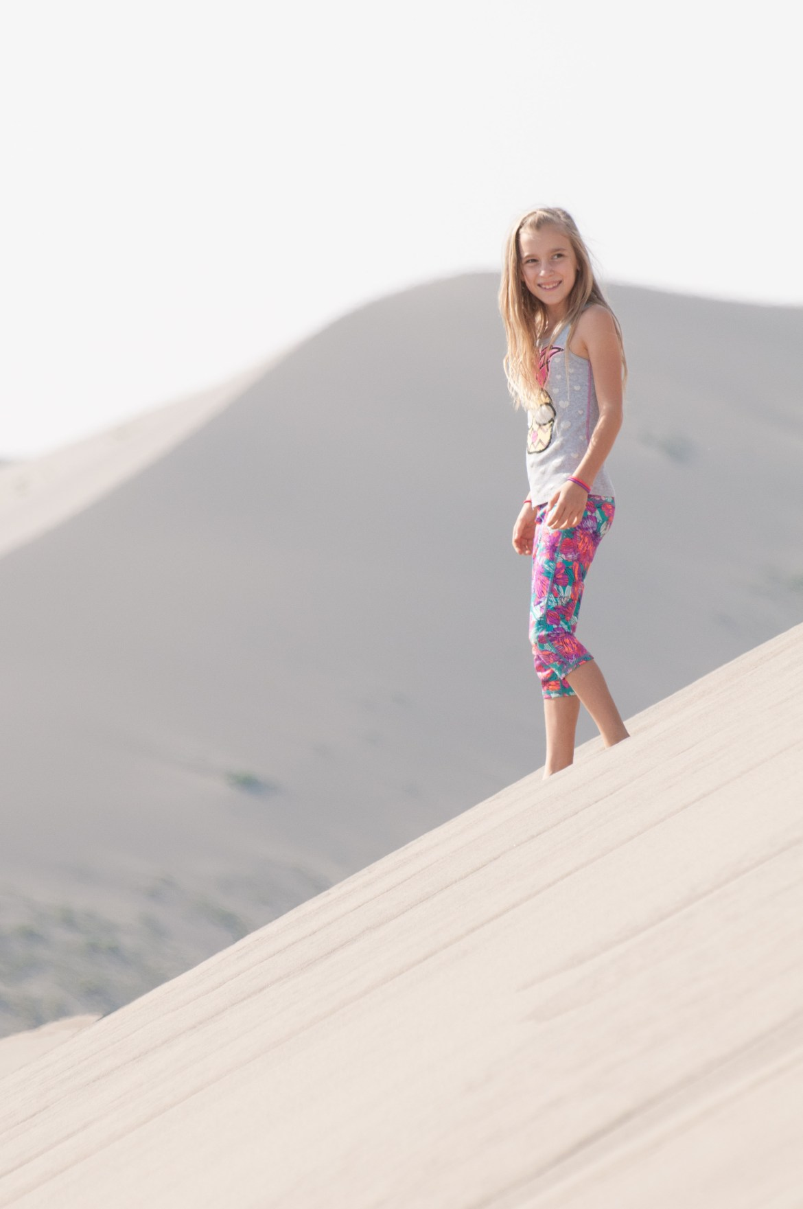 A young girl stands on a large sand dune at Southwest Idaho's Bruneau Sand Dunes State Park. The dunes are the largest free-standing sand dunes in North America.