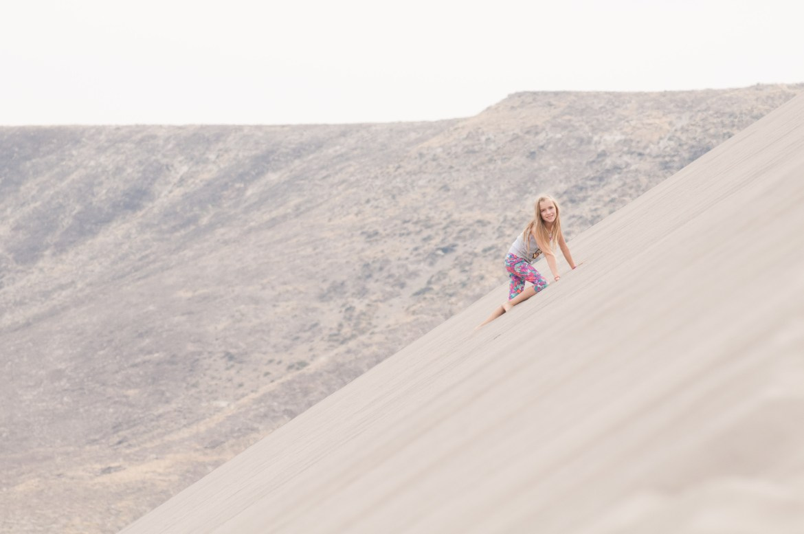A young girl hikes up a 45-degree sand dune at Bruneau Sand Dunes in Southwestern Idaho.  Bruneau Sand Dunes is the tallest free-standing dune in North America.