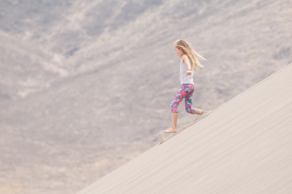 A young girl runs down a 45-degree side of the largest sand dune at Southwest Idaho's Bruneau Sand Dunes State Park. The dunes are the largest free-standing sand dunes in North America.