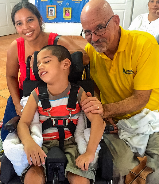 The Late Jacqui, a Locally Trained Therapist, and Chuck, a Retired Occupational Therapist, with a Client in a Brand New Specialized Wheelchair Donated by the Coronado, Panama, Rotary Club (©simon@myeclecticimages.com)