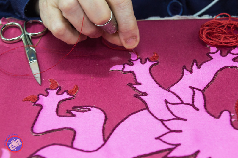 Stitching Segments of a Coat of Arms to Its Backing (©simon@myeclecticimages.com)