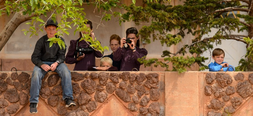 A group of FLDS children, themselves facing eviction, watch and take photos of a woman being evicted from a home in Colorado City, AZ, Tuesday May 9, 2017.
