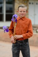 An FLDS boy stands in front of the Colorado City, Ariz., home he is being evicted from, holding flowers he would later leave on the hood of a UEP Trust employee's truck, Tuesday May 9, 2017.