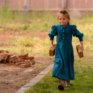 A young FLDS girl helps load a stack of bricks after her and about a dozen women and children were evicted from a Colorado City, Ariz., home, Tuesday May 9, 2017.