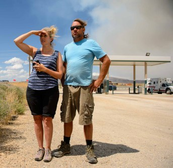 (Trent Nelson | The Salt Lake Tribune) Joann and Brent Yorga look on from Fruitland as their home in Serenity Ridge appears to be consumed by the Dollar Ridge Fire in Duchesne County on July 3.
