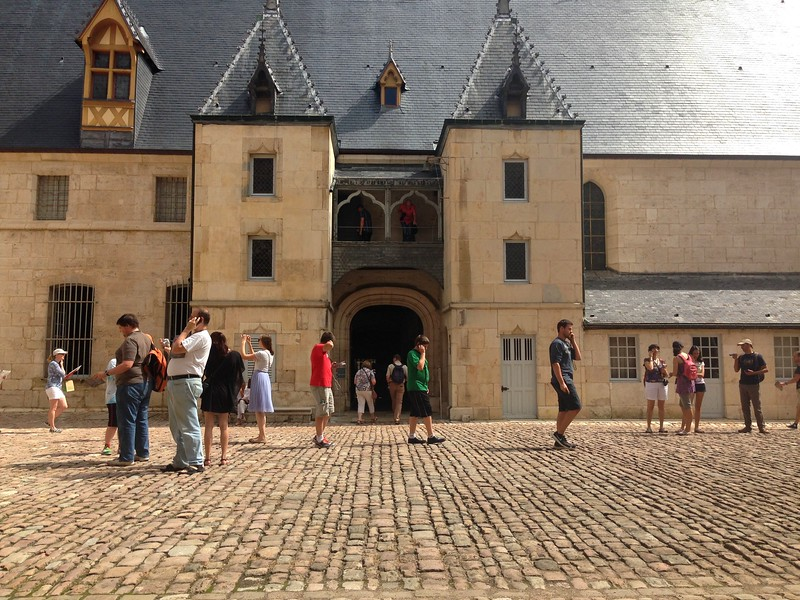 Visitors Listening to Audioguides in the Courtyard of the Hospices de Beaune in France