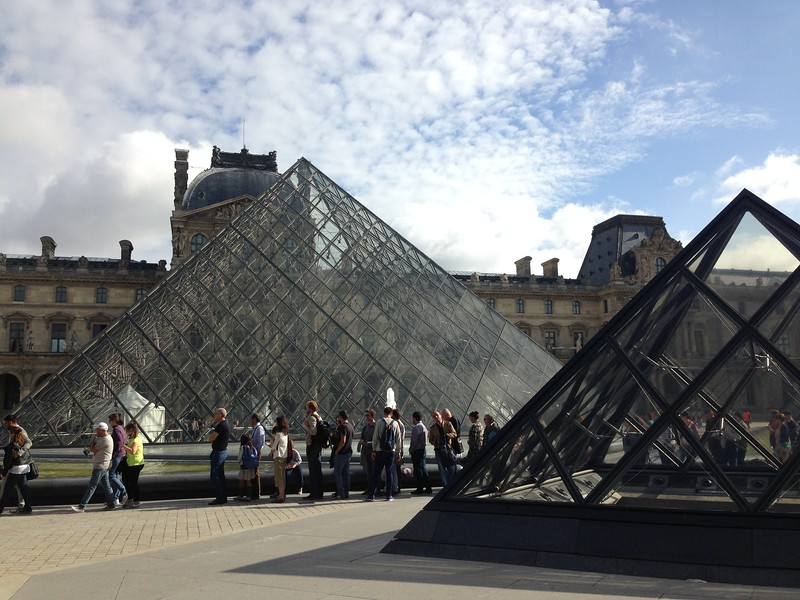A Line of People Winds Around the Pyramids of the Louvre, Paris