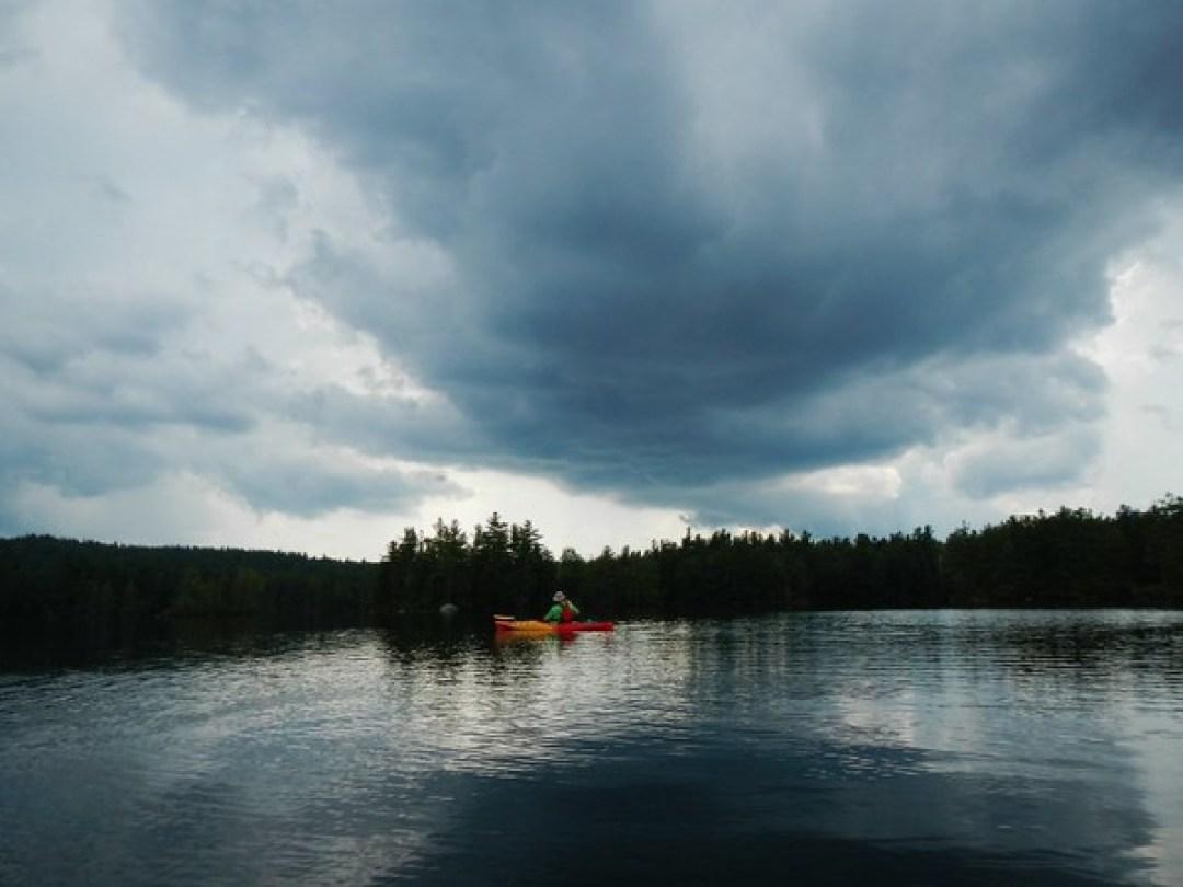 Frank kayaking below threatening clouds