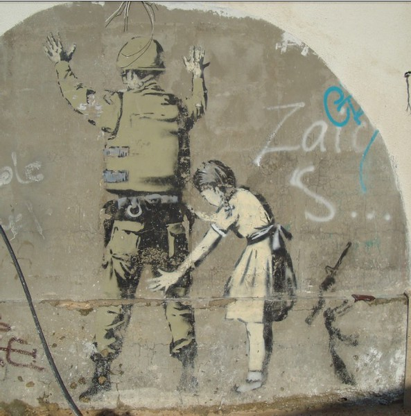 street art in Bethlehem girl frisking army man