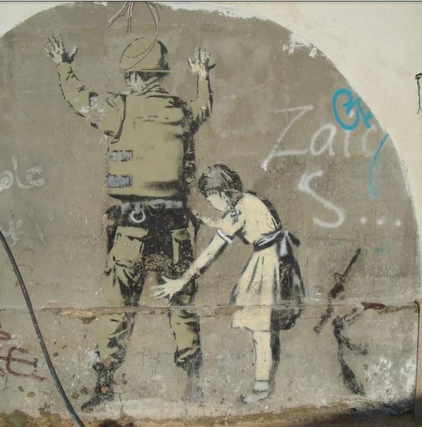 street art in Bethlehem girl frisking army man