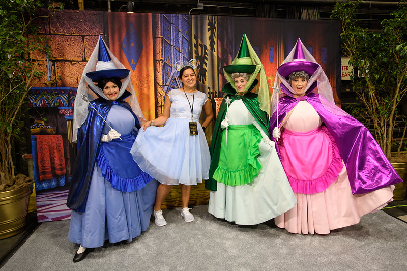 A guest poses with Sleeping Beauty's Flora, Fauna, and<br /> Merryweather at D23's 10-Year FAN-niversary Celebration at the Walt<br /> Disney Studios, March 10, 2019.