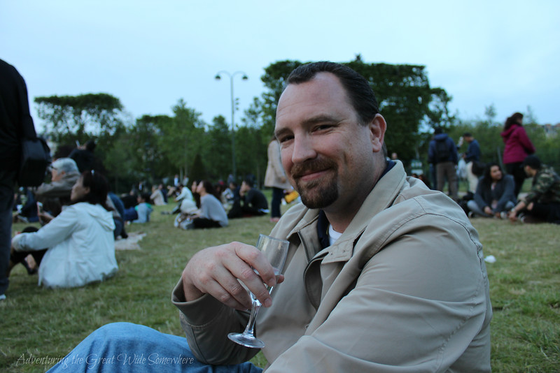 Dan smiling while holding a glass of champagne on the lawn beneath the Eiffel Tower.