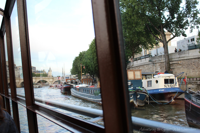 View of various boats tied up along the Seine, seen from inside our Bateaux Mouches dinner cruise