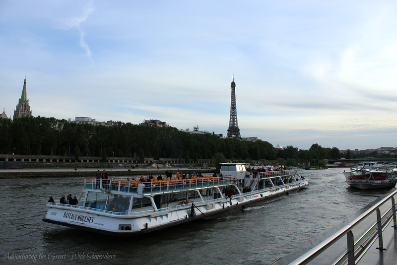 A Bateaux Mouches sightseeing boat cruises along the Seine, with the Eiffel Tower in the background