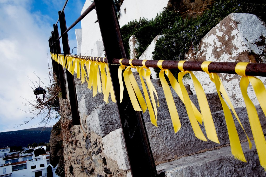 yellow flags tied to a railing