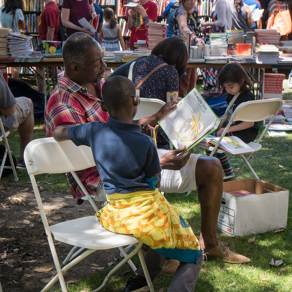 Parents reading to their children at the Festival of Books