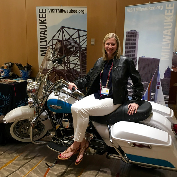 Brianne Miers sitting on a Harley Davidson