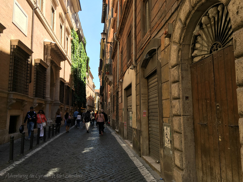 A narrow alley in Rome with beautiful dark cobblestones and endless beautiful doors