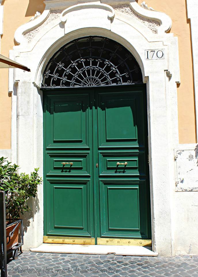 Emerald green door on a white and yellow building in Rome, Italy