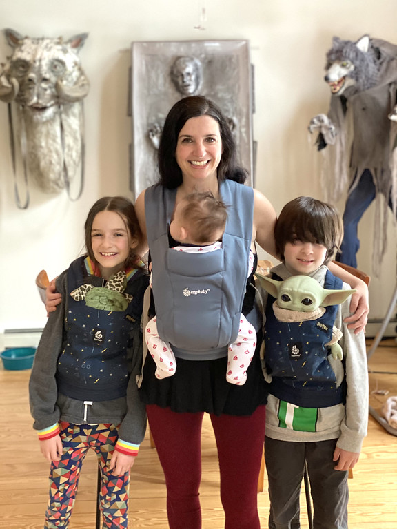 mom carrying baby in ergo embrace carrier with two older kids