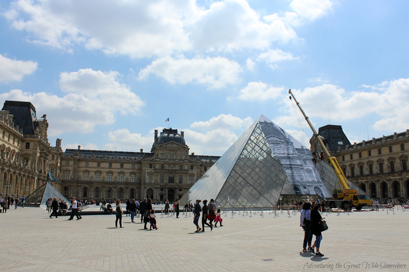 View of the Louvre courtyard and famous glass pyramid, which is being covered in a temporary art installation.