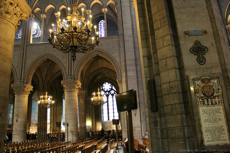 View of the chandeliers, arches and seats inside Notre Dame. Image is taken from the right side of the cathedral, looking across to the left side.