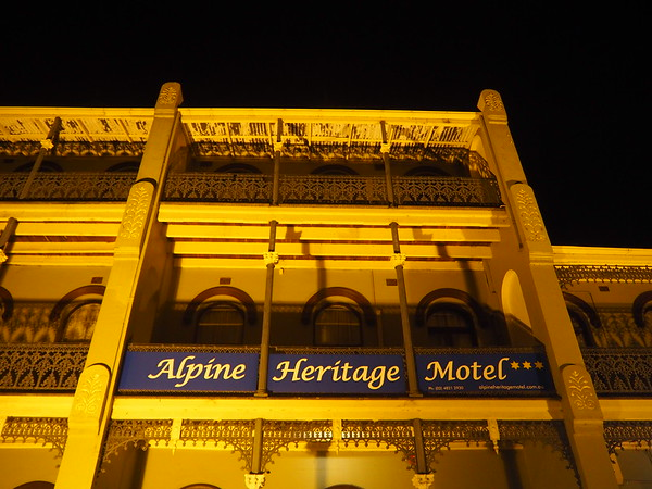 A three-story, 19th century building flood lit at night with a sign