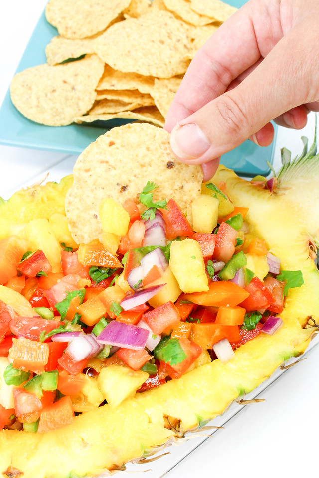 Pineapple Salsa is so fresh and delicious and very festive when served out of a pineapple. Enjoy it for all your end of summer/Labor Day party needs #recipe