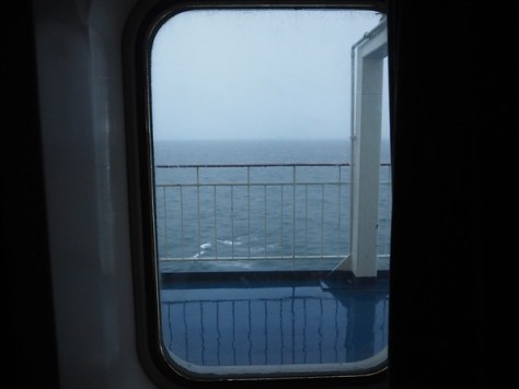 A view of a rainy morning at sea taken from a cabin window.
