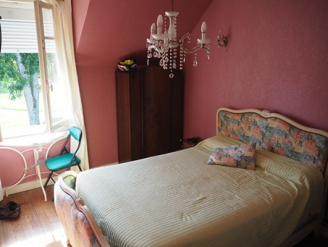 A double bed beneath a cheap chandelier in a pink-walled hotel room.