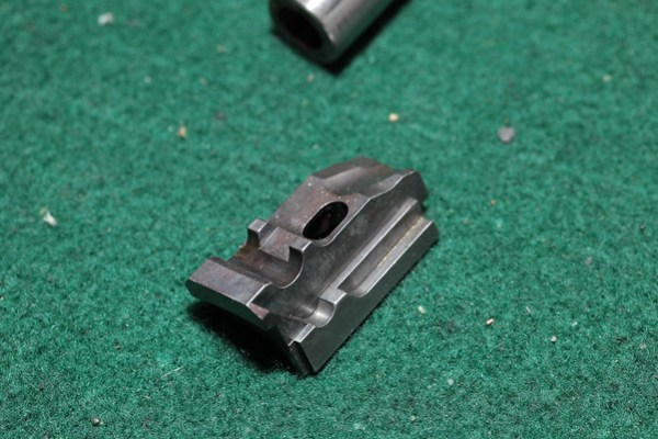 The unlock block. The way this part fits in the gun is with the top side in the picture pointing down. The bottom is on the barrel and the tongs ride on the angled part away from the picture.