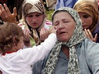 A child wipes the tears of its grandmother's face as trucks carrying 505 victims of the Srebrenica massacre roll down the main street of Sarajevo, Saturday, July 8, 2006. The trucks loaded with the coffins of newly identified victims of Europe's worst massacre since World War II stopped for a few moments in Sarajevo on Saturday to allow hundreds of people to pay tribute to their beloved ones. The bodies will be buried at Srebrenica on the 11th anniversary of the massacre on Tuesday. (AP Photo/Hidajet Delic)(AP Photo/Hidajet Delic)