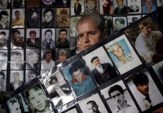 Bosniak (Bosnian Muslim) woman Hajra Catic, 60, who is a survivor of the Srebrenica massacre stands next to dozens of photos of the missing Srebrenica citizens, after this safe U.N. enclave fell into Bosnian Serb hands in July 1995, at the Association of Srebrenica widows in Tuzla, on Friday, July 7, 2006. Preparations are being made for the upcoming funeral of 500 victims on the 11th anniversary of the fall of Srebrenica. The 500 newly identified bodies of Muslims killed in the worst massacre of civilians since World War II will be buried next Tuesday.(AP Photo/Amel Emric)