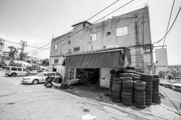 Autowerkstatt mit vielen gebrauchten Reifen in einem Gebäude in verbreiteter Architektur in Tiberias, Israel. Juli 2017 // Garage with a lot of used tires in front of the entrancy. Building has a typical middle east architecture style. Tiberias, Israel. July 2017