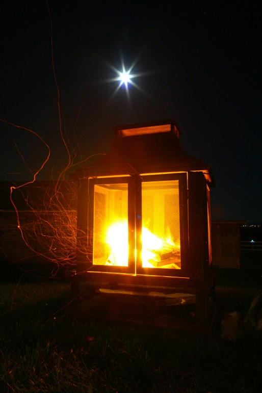Feuer in einem Kamin in der Nacht in Freien auf der Ile de Orleans, Quebec, Kanada. September 2015 // Wood fire in a fire place at the nighttime on the Ile the Orleans, Quebec, Canada. September 2015