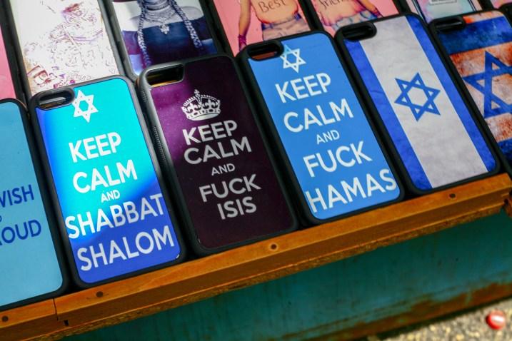 """Auf einem Marktstand werden Handy Covers angeboten mit der Aufschrift ,,Keep Calm and Fuck Hamas"""" sowie ,,Keep Calm and Fuck ISIS"""""""" sowie ,,Keep Calm and Shabbat Shalom"""". Tel Aviv, Israel. Juli 2017 // Handycovers saying ,,Keep Calm and Fuck ISIS"""" ,,Keep Calm and Shabbat Shalom"""" and ,,Keep Calm and Fuck Hamas"""" are offered in a bazarin Tel Aviv, Israel. July 2017"""
