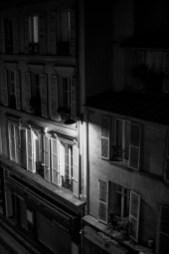 Altes Stadthaus mit hölzernen Fensterläden wird in der Nacht durch eine Laterne beleuchtet in Paris, Frankreich. Dezember 2016 // Old city building with wooden window shutters is enlighted of a street light in the night in Paris, France. December 2016.