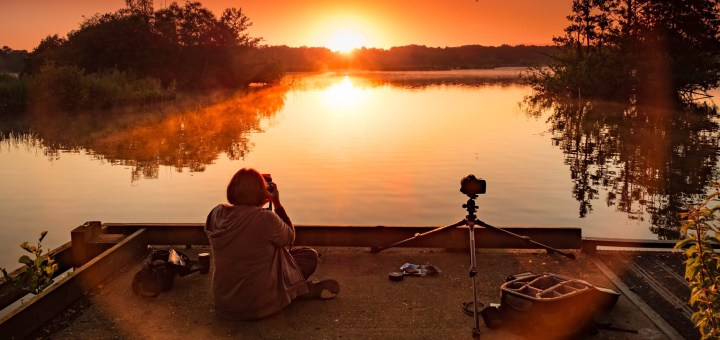 Photographer capturing sunrise at Fleet Pond in Hampshire