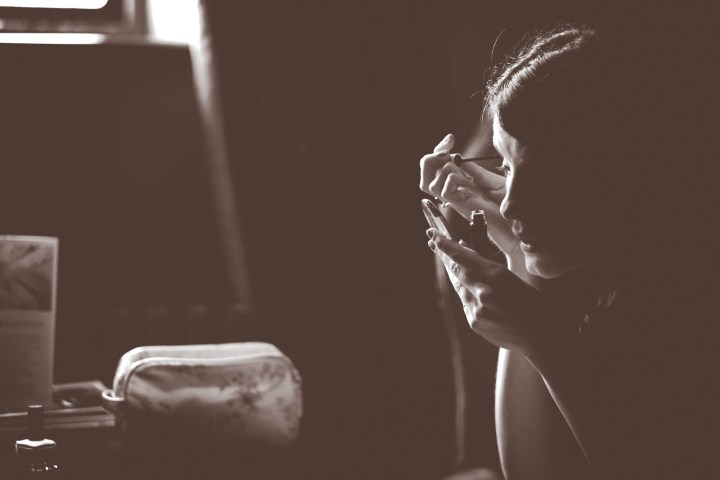 Silhouetted girl adding make-up