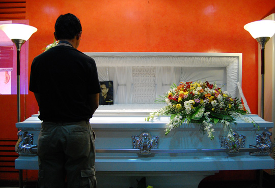 Toch Arellano's mortal remains lie in state at the Marian Chapels, Mariano Marcos Highway, Antipolo. The FPPF went there in full force, led by Chairwoman Mrs. Eduviges Y. Huang and Project Director Lito Beltran, to pay their last respects to the master portraitist. Photo shows Photographer Vic Sison viewing the remains of his fallen colleague. Photo by Chris Malinao.