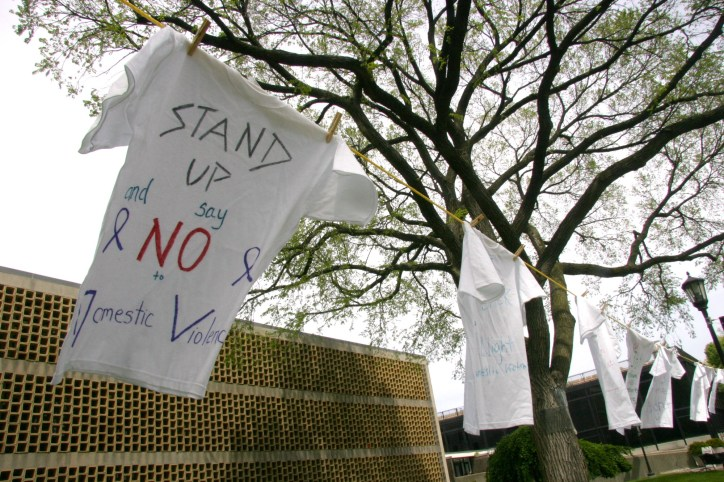 Students' messages against domestic violence are written on t-shirts to promote awareness.