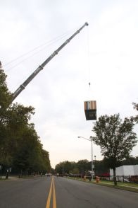 Hoisted by a 600-ton crane, a module goes from the parking lot, over Goulden Avenue, to the construction site.