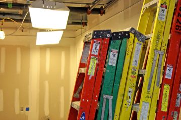 Ladders are stacked in a room where pipes and wiring will eventually get hidden behind a ceiling.