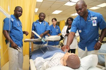 An instructor looks over as nursing students are making a diagnosis and administering a treatment.