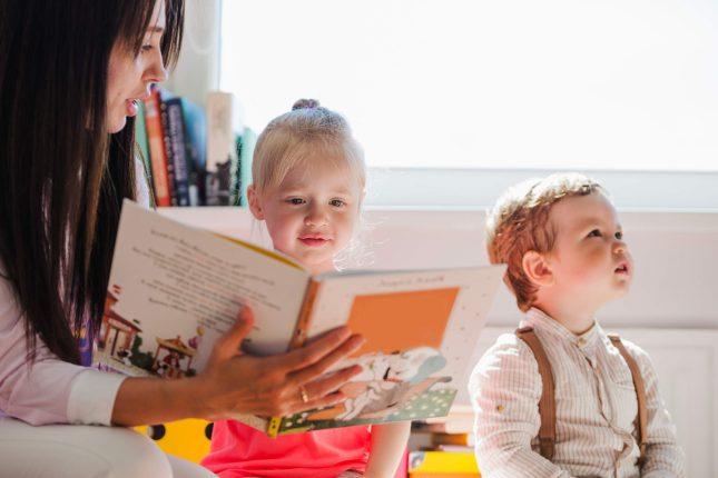 Maestra che legge un libro ai bambini all'asilo nido
