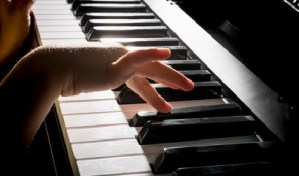 child's hands playing the piano