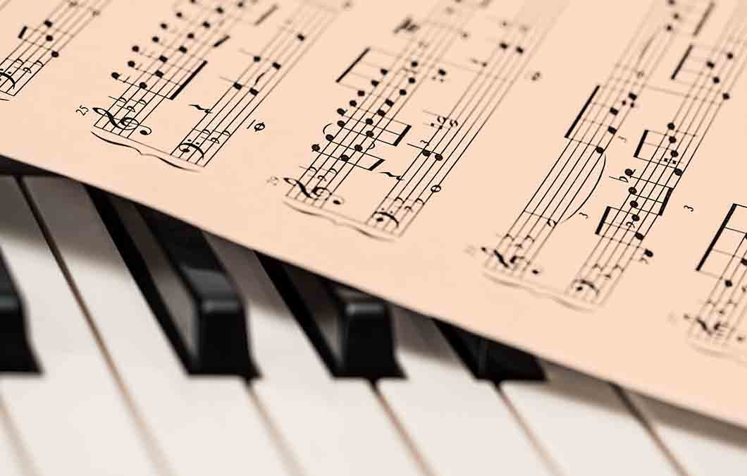 piano sheet music laying on keyboard