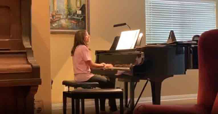 Picture of student at the piano with John Douglas accompanying her